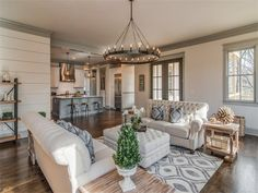 Like the ship lap walls and overall neutral. Neutral Living Room Candelabra-style Chandelier and Rustic Reclaimed Wood Accents. Greige Painted Window Trim and Crown Moulding | Nashville, Tennessee | The Lipman Group Sotheby's International Realty