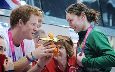 Charm offensive: Britain's Prince Harry is given a mascot by Australian swimmer Maddison Elliott - Australia's youngest ever paralympian  Picture: GETTY IMAGES