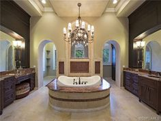Spacious bathroom with his and hers vanities - large soaking tub (directly under that heavy chandelier!!) and walk through shower.  Ahhhhhh......  Port Royal in Naples, FL