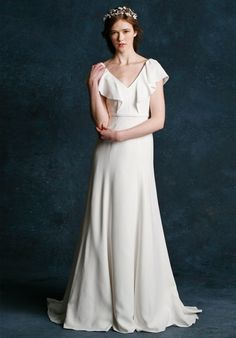 The Chelsea features a V-neckline and a plunging V-back with flutter sleeve detail for a romantic look. The skirt has a slight fit through the hip giving the dress a modified trumpet silhouette.