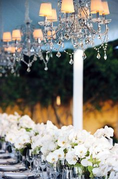 Pair classic Dendrobium orchids with silver votives and chandeliers for a modern, elegant wedding reception.