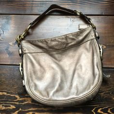 "100% authentic coach bag Pre-loved but still has a lot of life left! Body has some scratches and wear not super noticeable , under strap has some green lines (see photo). 12"" wide 9"" tall. Bronze color. Coach Bags Satchels"