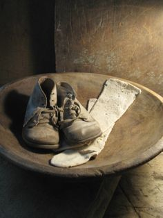 The old treen bowl holds shoes once white and worn, and knit stockings of a very young child.  HighButtonShoe.net