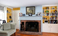 Living room with a wood-burning fireplace and a blue accent wall. Also includes built-in shelves and cabinets.
