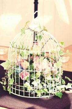 For a whimsical or garden themed wedding, use a birdcage as a centerpiece! Add in colourful flowers.