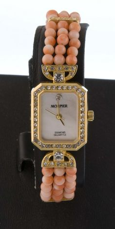 Morpier jeweled watch with coral bead bracelet.