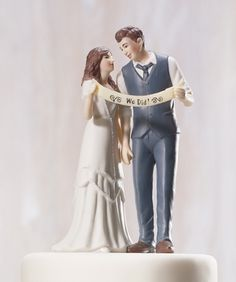"""-This trendsetting Couple's style is casual, cool and classic. The retro inspired attire and hairstyles are practically perfect for vintage themed weddings. This Couple stares lovingly into each other's eyes while confidently holding up a banner declaring """"We Did!"""".   Product Material:Hand Painted Porcelain   Cake top measures 4 7/8"""" tall"""