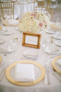 Reception table setting: gold-rimmed glass plates and gold-framed table names | Chicago Botanic Garden Wedding | Jenelle Kappe Photography