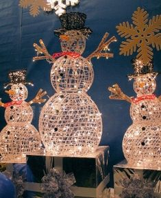 Snowmen of varying heights are created by placing staggered wrapped Christmas boxes underneath. The boxes are wrapped in a metallic silver which reflects beautiful Christmas lights and colors. Large decorative white snowflakes hang from above.