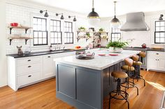 The U-shaped kitchen layout of the TOH North Shore Farmhouse Project revolves around a large marble-topped center island ideal for entertaining. Industrial touches include black hardware and steel-legged stools.