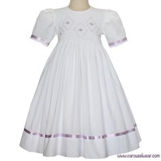 Lavender satin ribbon adds a soft touch to this classic Grace dress. Short sleeve silhouette with a fully smocked bodice girls dress. Hand embroidered lavender flowers with green leaves and white smoc