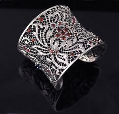 "Lydia Lerner Lace Flower Gemstone Cuff Made in Bali Sapphire, Peridot, Garnet, Champagne Citrine, Blue Topaz & Rubies Handmade & handset stones Sterling silver 80g Measures 1 1/8"" wide 2 1/8"" east to west diameter"
