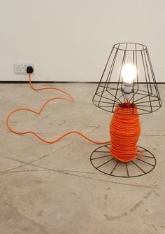 Up-cycled / recycled lamp with black wire shade and red orange cord.