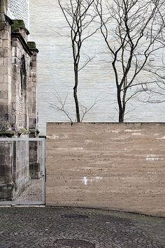 Kolumba Museum - Peter Zumthor.  rammed earth wall, stone paver patterning, block stone building, white ledgestone facade cladding