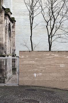 Kolumba Museum - Peter Zumthor.  rammed earth wall, stone paver patterning, block stone building, white ledgestone facade cladding