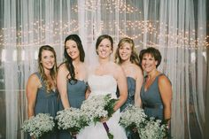 twinkle light barn wedding brides and bridesmaids in gray with baby's breath bouquets in front of mesh drapery. Green Villa Barn just 10min from Salem, Oregon