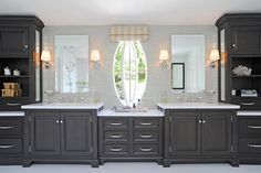 The 14-foot-long vanity in this luxurious master bathroom provides ample countertop space and cabinet storage. What makes the space truly unique is the unusual yet lovely oval window.