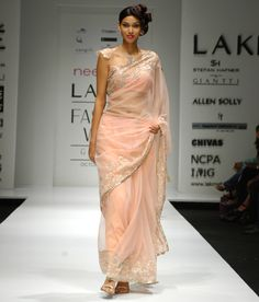 Peach chiffon and chantilly lace saree with a slim rhinestone border. The saree comes with a matching blouse.