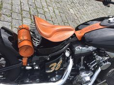 Saddle tan custom seat and leather accessories on black motorcycle