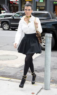 "Kourtney Kardashian wearing an Alice & Olivia top, Acne skirt, American Apparel tights, YSL shoes, Prada collar and ankle cuffs, Patricia Field ""I'm an Icon"" necklace and a Christan Louboutin bag."