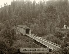 """Wooden covered bridge @ Clackamas River at Carver, reported to have been the longest covered bridge in Oregon at the time of its completion. Horace Baker, who previously operated a slack-line ferry at this spot. Today's steel bridge at the same location is still referred to as the Baker Bridge. In detail view 1, you can see a sign above the entrance to the bridge. On an actual print, you can just make out its message: """"$25 Fine for Driving or Riding Faster than a Walk on this Bridge"""