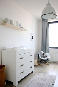 Mooie simpele kamer met lichte kleuren en houten wandplank