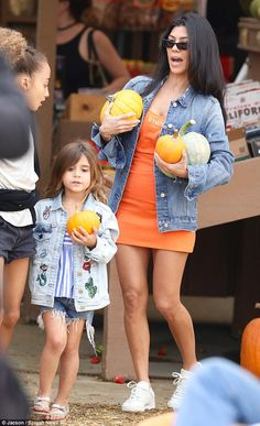 Boo! Kourtney Kardashian got into the Halloween spirit by donning an orange mini-dress to buy pumpkins at Underwood Family Farms in Moorpark on Sunday with daughter Penelope