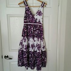 Gorgeous purple spring / summer dress. This dress is 100% cotton . This dress has a 14 in waist  unstretched & a length of 42 in. As you can see by one of the pictures the straps are adjustable with buttons. On the close up picture of the white on the dress you can see some color exchange. I bought it that way and did not feel it was noticeable. magic Dresses