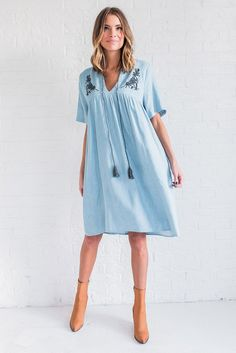 DETAILS:  Embroidered denim dress Front tie tassel Knee Length Fabric Content: 100% Cotton Model is wearing a small