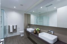 Minimalist white and wood bathroom with two white sinks and glass shower stall