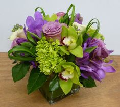This is a cube vase floral arrangement that features roses, hydrangea, cymbidium orchids and mokara orchids in a lavender and green color scheme with lily grass loops.  See our entire selection at www.starflor.com.  To purchase any of our floral selections, as gifts or décor, please call us at 800.520.8999 or visit our e-commerce portal at www.Starbrightnyc.com. This composition of flowers is generally available for same day delivery in New York City (NYC).   SQ303