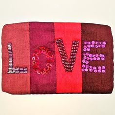 This fun and funky 'LOVE' zip purse makes a great gift or treat for you. The rich silk effect fabric cover is hand embroidered with beads and sequins for Namaste on a fair trade basis. Made from polysilk.  This purse is mainly 'Pinks' - we also stock 'Multi' and 'Blues', under different stock codes.  Width : 155mm Height : 100mm Thickness : 15mm