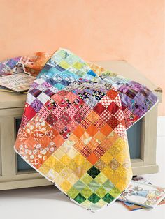 This scrappy baby quilt features 16-patch blocks, each of one color from the rainbow. Digital pattern available!