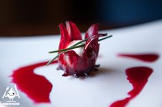 Goat Cheese nestled in a Wild Hibiscus Flower with Chive served with a drizzle of the Hibiscus Flower Syrup.