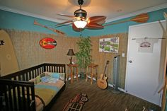 """Kielans Surf / Skate Room!!, My son is now 2 1/2, so it was time to update his baby room to make it geared toward his interests now as a 2 1/2 year old - he loves to surf, skateboard and stand-up paddle, so I wanted to make a fun space for him to hang out!  , To give it the """"tiki/tropical"""" look, I bought some bamboo reed at Lowes and nailed it up around the room.  Its really hot here in Hawaii, so we have a ceiling fan in his room that is in the shape of surf boards. The lamp in the corner…"""
