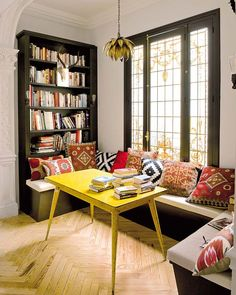 the graphically clean yellow table, the raw wood herringbone floors, the kilim pillows, the antlers on the bookshelf, the gold pendant light all add up to a most interesting hallway nook for reading and playing games. eclectic and boho and decorated. desiretoinspire.net - Luminous beauty