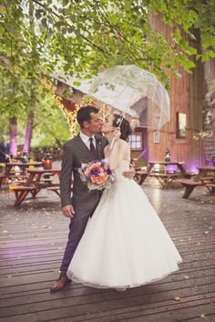 A clear umbrella makes for sweet rainy day wedding photos