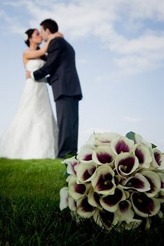 bouquet in foreground, couple in background; photo by james thompson
