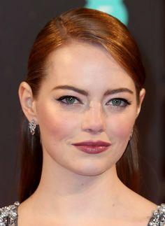 Emma Stone linda com batom cor de boca meio vinho e cabelo minimal solto com risca lateral