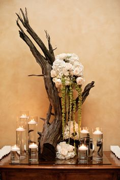 A striking centerpiece was composed of a bare branch accented with bouquets of ivory roses and hydrangeas, green amaranthus, and floating candles. #centerpiece Photography: Kristen Weaver Photography. Read More: http://www.insideweddings.com/weddings/a-tuscan-themed-jewish-wedding-in-florida-with-natural-details/654/