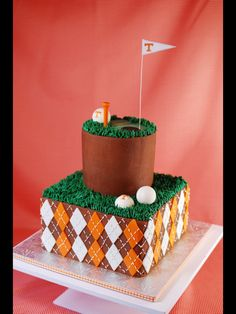 """""""Chocolate buttercream with fondant diamonds, buttercream grass and white chocolate gold balls. Used edible images for the T on the gold balls. Gumpaste for the Ts with a wire inserted so they would stand up."""""""