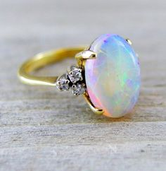 Georgeus! vintage opal and diamond ring featuring a 3.04 carat white opal accented by 0.08 carats of round brilliant cut diamonds. The opal exhibits