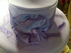 Tall crown with lavender poofs and applique on gray