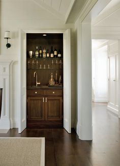 built-in wet bar by Matthew Sapera . beautiful dark wood bar behind double doors