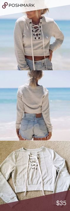 Gray Lace Up Cropped Sweatshirt M Super cute gray cropped sweatshirt with lace up detailing. Looks awesome with denim high waisted shorts for the spring/summer! Brand new, never worn. Boutique brand. Size medium. Boutique Tops Sweatshirts & Hoodies
