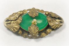 I love the romantic look of this Art Nouveau Brooch. The setting appears to be a gold tone or plated antique brass. Detailed Acanthus leaves