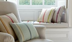 James Hare - Oriel Silks Fabric Collection - Multicoloured light striped fabric made into scatter and window seat cushions, with a plain cream-beige padded armchair Silk Wallpaper, Window Seat Cushions, Blinds Design, Roman Blinds, Striped Fabrics, Silk Fabric, Armchair, Hare, Throw Pillows
