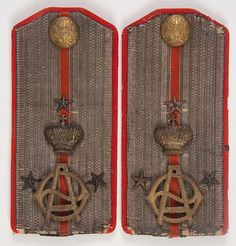 Imperial Russian shoulder boards of a Lieutenant for the Crimean Horse Her Highness Aleksandra Feodorovna Regiment. S ilver embroidered stripes on a red wool field and set with the cipher of Aleksandra Feodorovna beneath the Imperial crown..