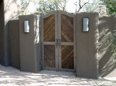 Stucco wall with lights on either side on wood gate.