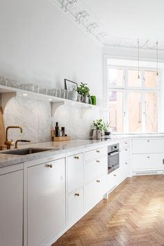 swedish eat in kitchen in white with brass pendants via coco kelley